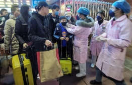 This photo taken on January 22, 2020 shows a staff member (center R) checking body temperature of a passenger at the Yingtan North Railway Station in Nanchang in China's central Jiangxi province.  (Photo by STR / AFP) /