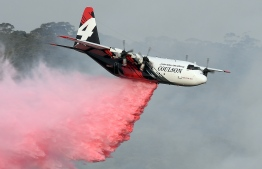 "(FILES) This file photo taken on January 10, 2020 shows a C-130 Hercules plane from the New South Wales Rural Fire Service dropping fire retardent to protect a property during an operation to douse bushfires in Penrose, in Australia's New South Wales state. - Three people died when a C-130 Hercules water-bombing plane crashed southwest of Sydney on January 23, 2020, setting off a ""large fireball"", Australian officials said, as bushfires flared across the country's southeast. (Photo by SAEED KHAN / AFP)"