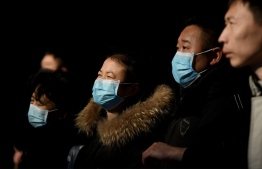 Passengers wearing protective facemasks to help stop the spread of a deadly SARS-like virus which originated in the central city of Wuhan arrive at Beijing railway station in Beijing on January 24, 2020. - China sealed off millions more people near the epicentre of a virus outbreak on January 24, shutting down public transport in an eighth city in an unprecedented quarantine effort as the death toll from the disease climbed to 26. (Photo by Noel Celis / AFP)