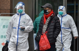 Medical staff wearing clothing to protect against a previously unknown virus walk outside a hospital in Wuhan on January 26, 2020, a city at the epicentre of the coronavirus outbreak. The virus has now been detected in UAE as well. (Photo by Hector RETAMAL / AFP)