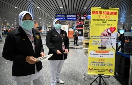 Malaysian health officers are deployed at Kuala Lumpur International Airport in Sepang on January 21, 2020 as authorities increased measure against coronavirus. (Photo by MOHD RASFAN / AFP)