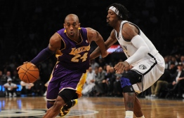 (FILES) In this file photo taken on February 05, 2013 Los Angeles Lakers' Kobe Bryant drives the ball past Brooklyn Nets Gerald Wallace during their NBA game at the Barclays Center in the Brooklyn borough of New York City. - NBA legend Kobe Bryant died Sunday when a helicopter crashed and burst into flames in foggy conditions in suburban Los Angeles, killing all nine people on board and plunging the sports world into mourning. (Photo by Emmanuel DUNAND / AFP)