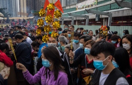 """People wear masks as they visit Wong Tai Sin temple on the first day of the Lunar New Year of the Rat in Hong Kong on January 25, 2020, as a preventative measure following a coronavirus outbreak which began in the Chinese city of Wuhan. - Hong Kong on January 25 declared a mystery virus outbreak as an """"emergency"""" -- the city's highest warning tier -- as authorities ramped up measures aimed at reducing the risk of further infections spreading. PHOTO: DALE DE LA REY / AFP"""