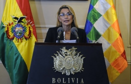 (FILES) In this file picture taken on November 13, 2019 Bolivia's interim president Jeanine Anez speaks during a press conference on her first day in power, at Quemado Presidential Palace in La Paz. - Anez asked for the resignation of all her ministers on January 26, 2020, two days after announcing she would stand in the May 3 presidential election and just hours after her Communications minister presented her resignation over such decision. A little-known senator, Anez assumed the presidency on November 12, two days aftern ow ex-president Evo Morales resigned following three weeks of sometimes violent protests against his controversial re-election in a poll the Organization of American States said was rigged. (Photo by JORGE BERNAL / AFP)