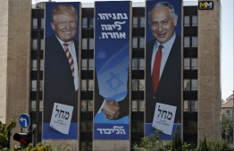 """(FILES) In this file photo taken on September 4, 2019, Israeli election banner for the Likud party showing US President Donald Trump shaking hands with Likud chairman and Prime Minister Benjamin Netanyahu hangs on the facade of a building in Jerusalem. - A peace plan with no chance of achieving peace: that's the paradox of Washington's proposal for an Israeli-Palestinian accord expected by January 28, 2020. A major obstacle to any such plan is that President Donald Trump has aligned himself so strongly with Israel, while repeatedly undercutting the Palestinian side, that in the eyes of the latter the US has lost its status as an """"honest broker."""" The plan, described by the American president as """"the ultimate deal,"""" seeks to bridge major gaps between the Israeli and Palestinian sides, a goal that has eluded previous administrations reaching back for decades. Trump's son-in-law and adviser Jared Kushner began working on the proposal in 2017 in a largely secretive process. (Photo by AHMAD GHARABLI / AFP)"""
