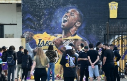 Fans gather to mourn the death of NBA legend Kobe Bryant at a mural near Staples Center in Los Angeles, California on January 27, 2020, a day after nine people were killed in the helicopter crash which claimed the life of the former Los Angeles Lakers star and his 13 year old daughter. - Nine people were killed in the helicopter crash which claimed the life of NBA star Kobe Bryant and his 13 year old daughter, Los Angeles officials confirmed on Sunday. Los Angeles County Sheriff Alex Villanueva said eight passengers and the pilot of the aircraft died in the accident. The helicopter crashed in foggy weather in the Los Angeles suburb of Calabasas. Authorities said firefighters received a call shortly at 9:47 am about the crash, which caused a brush fire on a hillside. (Photo by Frederic J. BROWN / AFP)