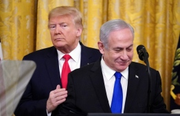 """US President Donald Trump and Israeli Prime Minister Benjamin Netanyahu take part in an announcement of Trump's Middle East peace plan in the East Room of the White House in Washington, DC on January 28, 2020. - Trump declared that Israel was taking a """"big step towards peace"""" as he unveiled a plan aimed at solving the Israeli-Palestinian conflict. """"Today, Israel takes a big step towards peace,"""" Trump said, standing alongside Netanyahu as he revealed details of the plan already emphatically rejected by the Palestinians. (Photo by MANDEL NGAN / AFP)"""