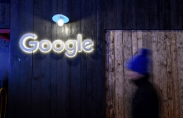 A man passes by a sign of Google at Google's stand during the annual meeting of the World Economic Forum (WEF) in Davos, on January 21, 2020. (Photo by Fabrice COFFRINI / AFP)