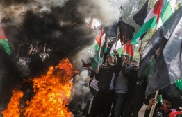 Palestinian demonstrators chant slogans and wave Palestinian flags as they stand by flaming tyres during a protest against US President Donald Trump's expected peace plan proposal in Gaza City on January 28, 2020. (Photo by MAHMUD HAMS / AFP)