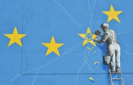 (FILES) This file photo taken on January 7, 2019 shows a mural by British artist Banksy, depicting a workman chipping away at one of the stars on a European Union (EU) themed flag,in Dover, south east England. - Britain leaves the European Union on January 31, ending more than four decades of economic, political and legal integration with its closest neighbours. (Photo by Glyn KIRK / AFP) /
