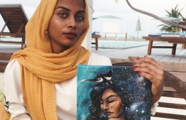 Local artist Samiyya Shehenaaz (Sam) holding up a self-portrait 'Underwater Galaxies' from her 'Youniverse' collection. The artwork displayed at Angsana Velavaru is the artist's second solo exhibition. PHOTO: SAM