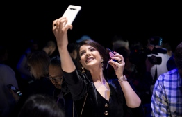 "Morrocan actress-model Leila Hadioui takes a selfie while holding a Samsung Galaxy Z Flip phone displayed during the Samsung Galaxy Unpacked 2020 event in San Francisco, California on February 11, 2020. - Samsung unveiled its second folding smartphone, a ""Z Flip"" handset with a lofty price tag aimed at ""trendsetters."" The smartphone flips open, like a pocket cosmetics case, opening into a 6.7-inch screen. (Photo by Josh Edelson / AFP)"