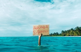 "A climate activist holds a sign which reads, ""are you waiting until we sink?"". PHOTO: TWITTER/ VISITLAAMU"